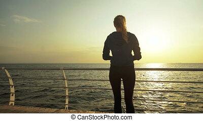 Attractive runner training for marathon in beautiful beach.