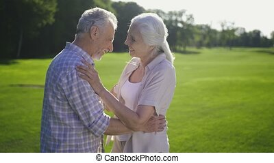 Attractive senior couple laughing on green lawn - Portrait...