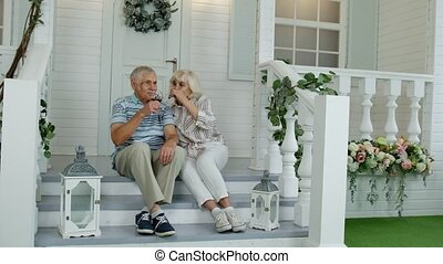 Attractive senior elderly Caucasian couple sitting and drinking wine in porch at home, making a kiss
