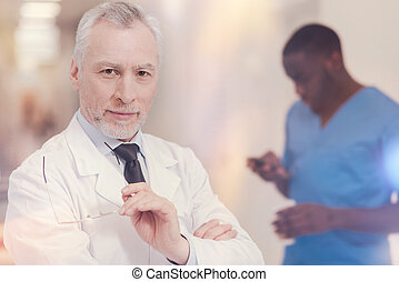 Attractive senior man holding glasses in his hands