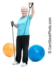 Attractive senior woman at health club, doing exercises with...
