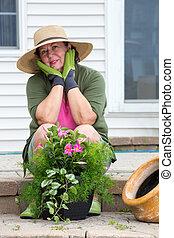 Attractive senior woman potting up plants