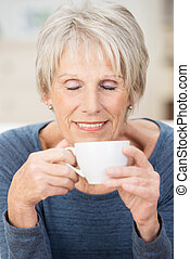 Attractive senior woman savoring a cup of coffee