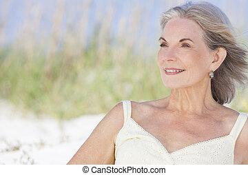 Attractive Senior Woman Sitting At Beach