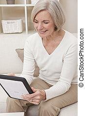 Attractive Senior Woman Using a Tablet Computer - Attractive...