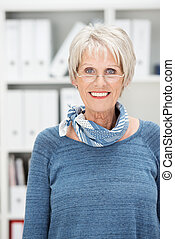 Attractive senior woman wearing glasses and a trendy scarf ...