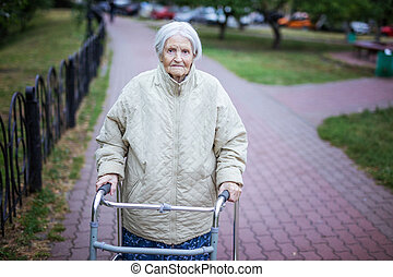 Attractive senior woman with walker outdoors