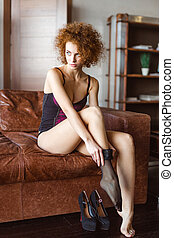 Attractive sensual young curly woman in corset wearing black stockings