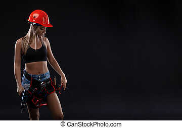 attractive sexy girl in safety helmet with tool belt holding electric drill on black background. Copy space.