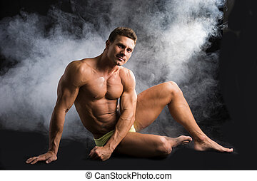 Attractive shirtless muscular man sitting on the floor in swimming suit