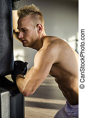 Attractive shirtless young man with boxing gloves
