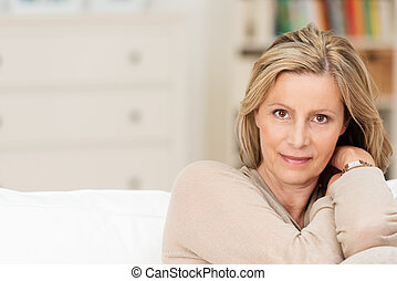 Attractive sincere middle-aged woman sitting on a sofa...