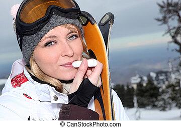 Attractive skier applying lip balm
