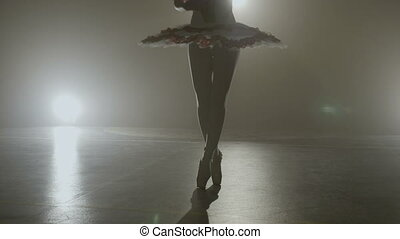 Attractive skinny ballerina silhouette in white tutu outfit dancing while warming up in a professional dark studio