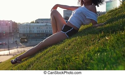 Attractive skinny mulatto woman lying on the grass in the...