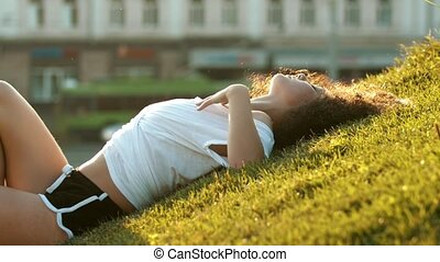 Attractive skinny young woman lying on the grass and hugging...