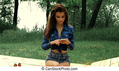 slender brunette in shirt sitting on a bench and looking in the telephone
