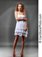 Attractive slender woman in simple white dress on light backgrou