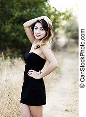 Attractive Slim Asian American Woman Outdoors In Black Dress