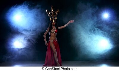 Attractive slim belly dancer go on dancing with candles, her...
