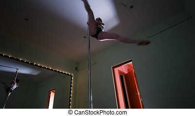 Attractive slim girl exercising pole dance in a studio