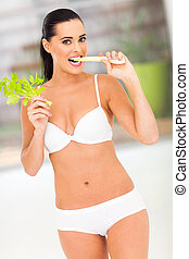 slim woman biting celery stick