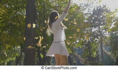 Attractive slim young girl having fun and enjoying freedom with autumn leaves and spinning in the park on a sunny day in slow motion