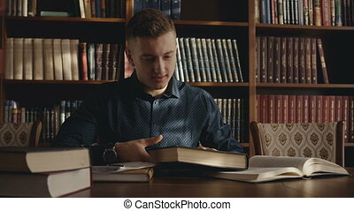 Attractive smart man in library is looking for information