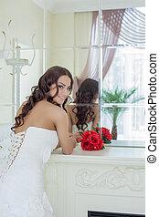 Attractive smiling bride posing in front of mirror