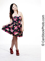 Smiling Chinese American Woman Standing In Floral Dress Holding Hem Up With Red Shoes