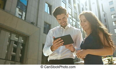 Attractive smiling colleague helping her friend to use tablet correctly.