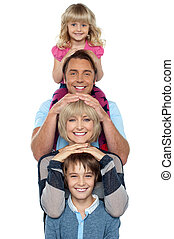 Attractive smiling family of four posing in a single line isolated over white background.