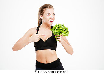 Attractive smiling fitness woman pointing finger at lettuce ...