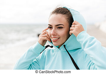 Attractive smiling healthy fitness woman wearing hoodie