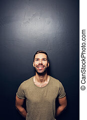 Attractive, smiling man leaning against the wall. Hapiness...