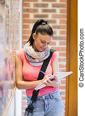 Attractive smiling student taking notes next to notice board