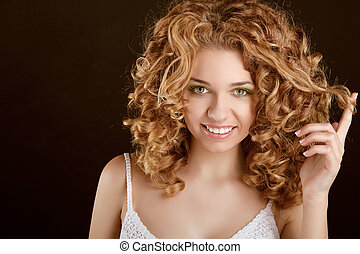 Attractive smiling teen girl with Curly Hair wavy hair, curl on finger