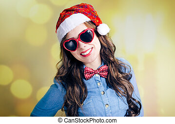 Attractive smiling teenage girl in Santa hat and sunglasses