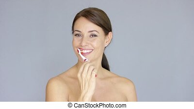 Attractive smiling woman brushing her teeth - Attractive...