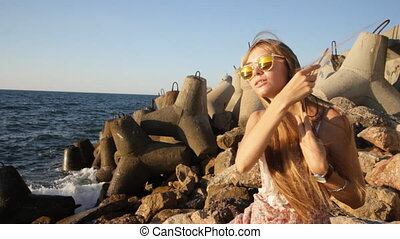 attractive smiling woman brushing her hair at the seashore
