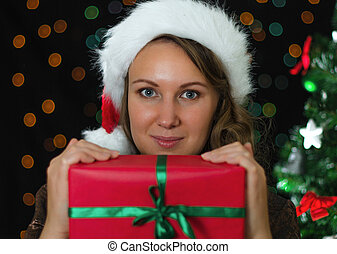 Attractive smiling woman holding christmas gift.