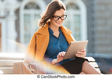 Attractive smiling woman in eyeglasses using tablet computer