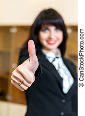 attractive smiling woman in office shows thumb up, ficus on a finger