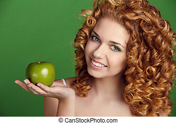 Attractive smiling woman portrait with long glossy hair holding apple over green