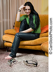 Attractive smiling woman relaxing and sitting on sofa at home