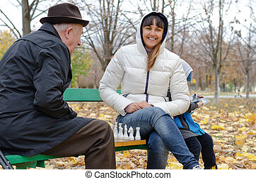 Attractive smiling woman sitting on a park bench playing chess with an elderly man
