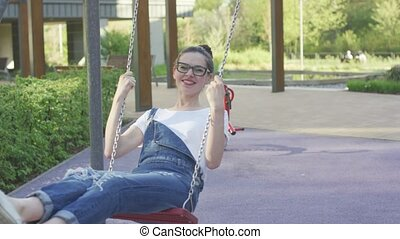 Attractive smiling woman swinging on playground - Young...