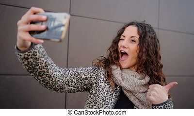 Attractive smiling woman taking selfies in the street.
