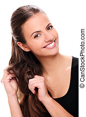 Attractive smiling woman touching her hair - Portrait of...