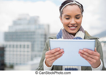 Attractive smiling woman using tablet while standing outside
